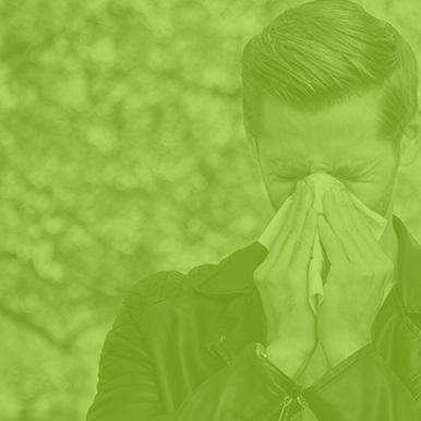 man with allergies blowing his nose as hard as he can, standing on right side of picture