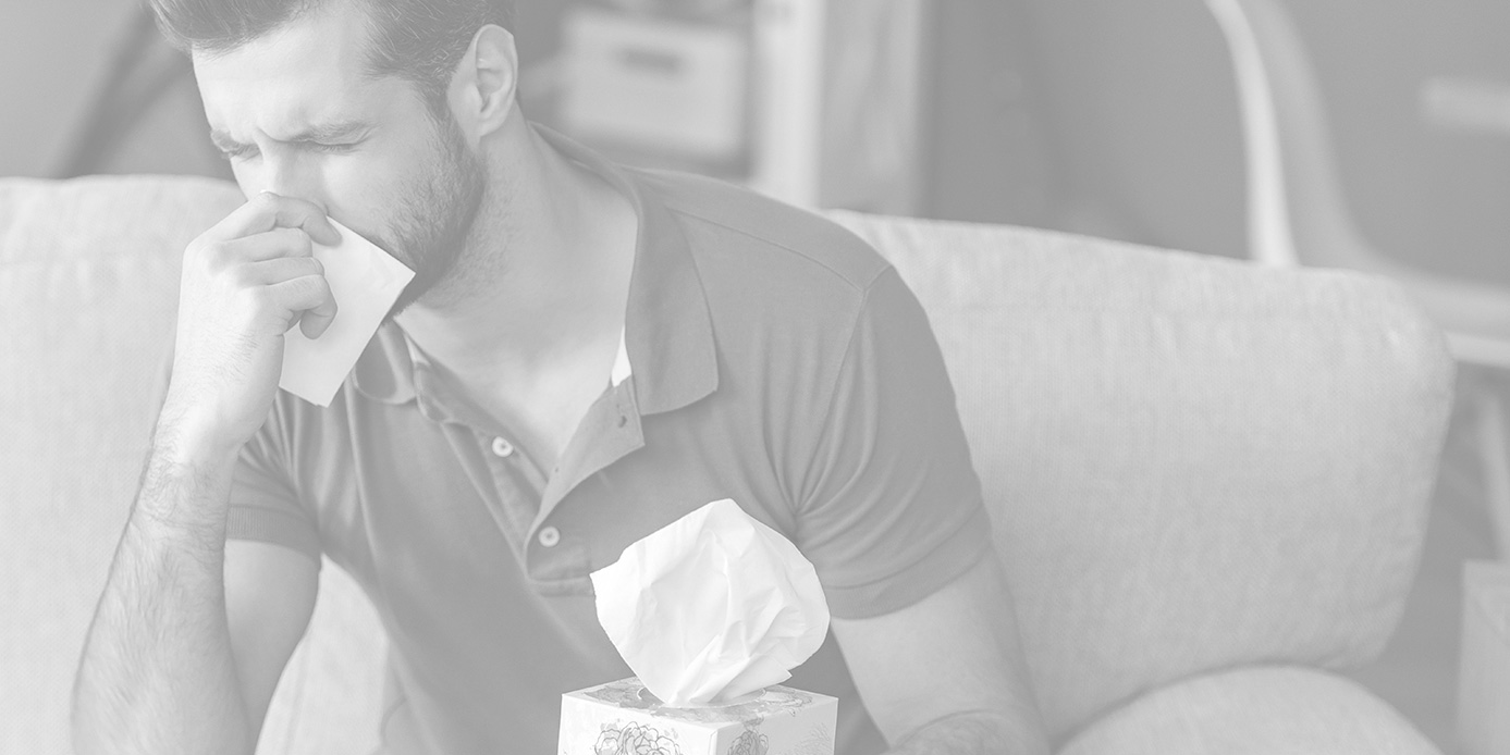 man sneezing into tissue while sitting on couch next to tissue box