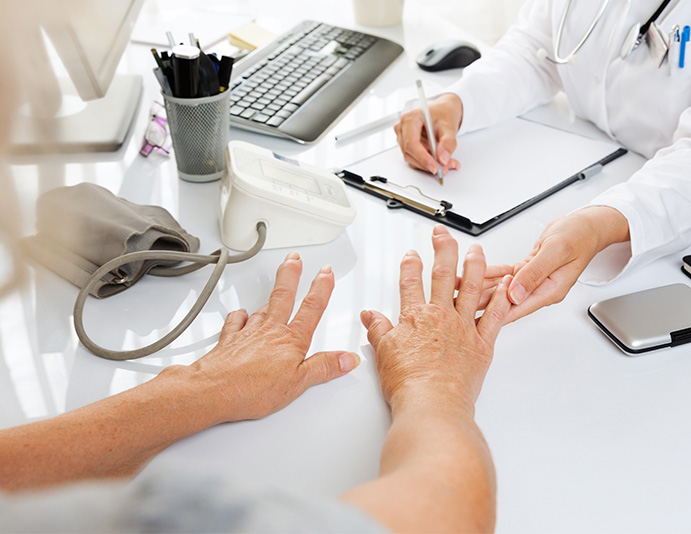 doctor holding senior man's finger while filling out paperwork