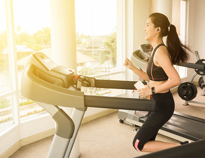 woman running on treadmill and listening to music using earbuds, having the time of her life