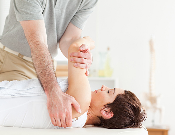 chiropractor helping woman with shoulder burstitis with guided arm stretch