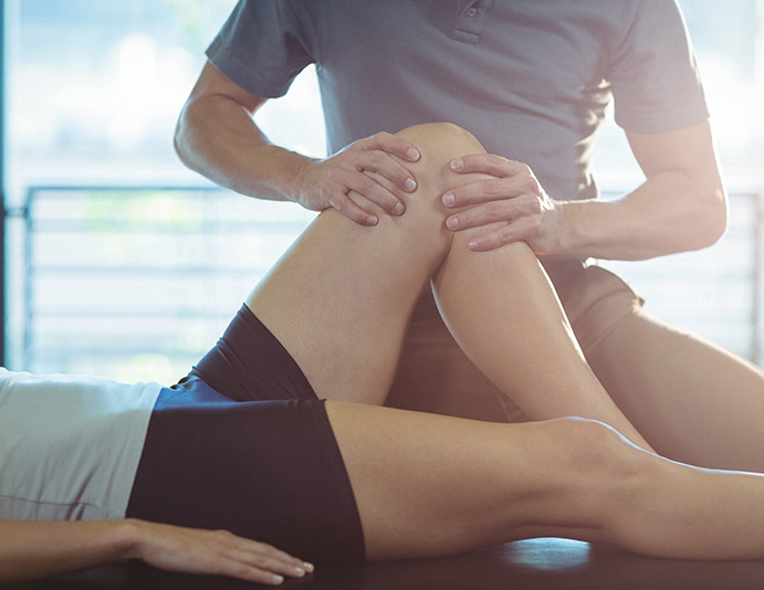 chiropractor stretching patient's knee to help with chronic knee pain