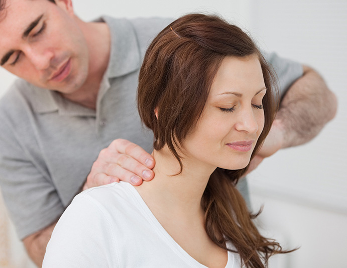 chiropractor giving woman careful massage around shoulders and neck