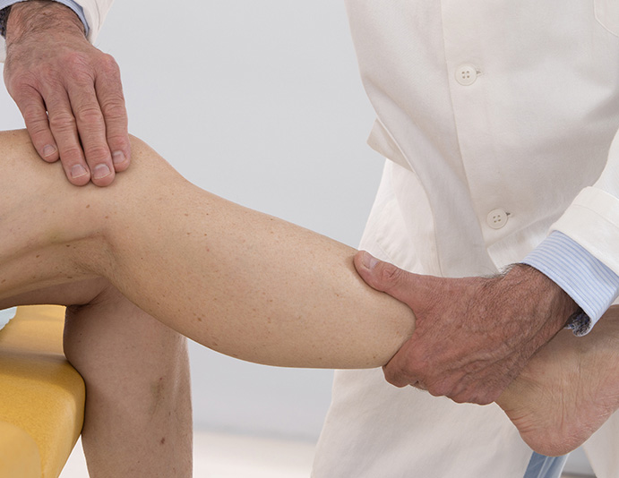 chiropractor checking muscle strength surrounding knee cap to determine knee health