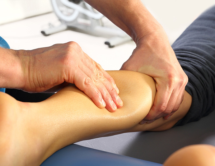 chiropractor applying pressure to patient's lower leg around shin