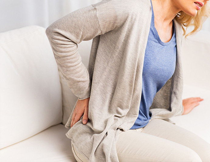 woman holding lower back on right side due to sciatica pain