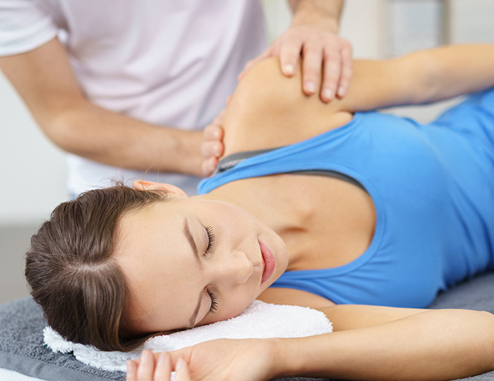 chiropractor easing patient's shoulder into slow stretch to rehabilitate shoulder