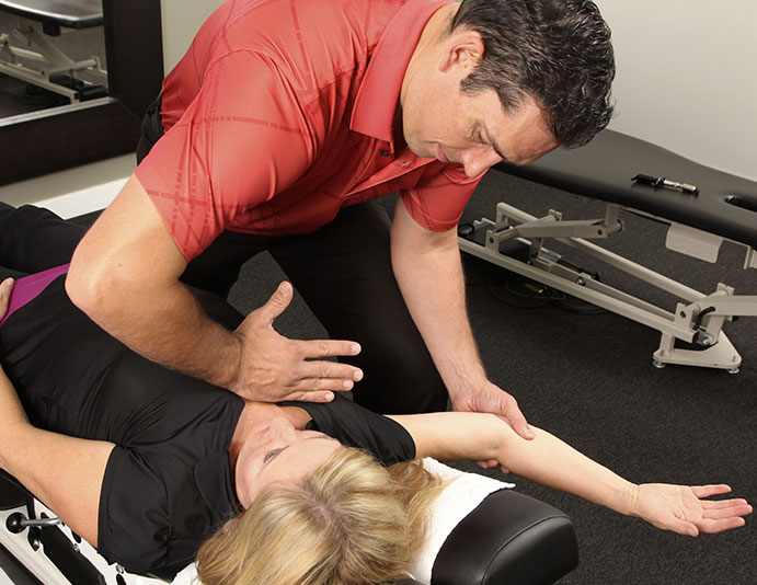 chiropractor applying pressure to patient's arm and shoulder muscle for shoulder adjustment