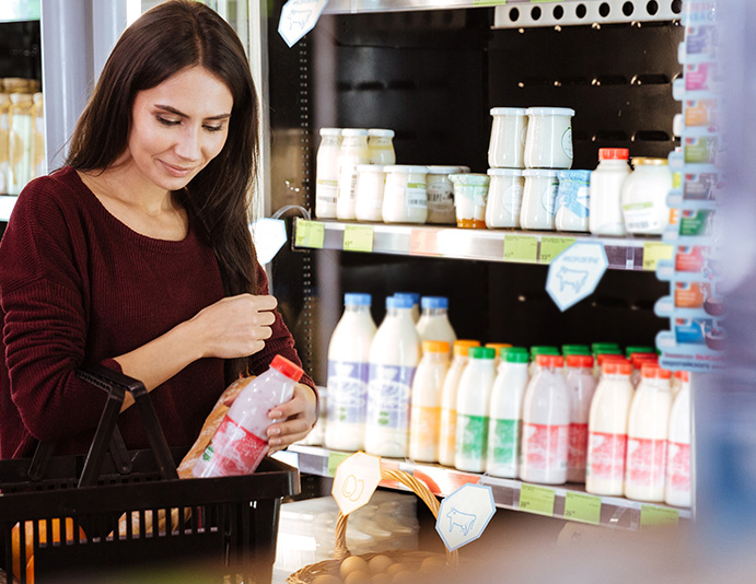 woman shopping for strawberry milk and smiling due to nutritious food choices