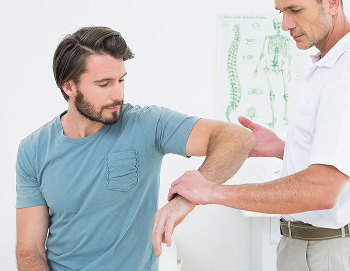 chiropractor guides patient's arm up and outward for shoulder adjustment