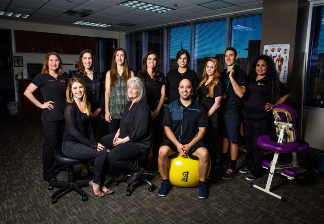 AFC Chiropractic Desert Ridge team posing together with exercise ball