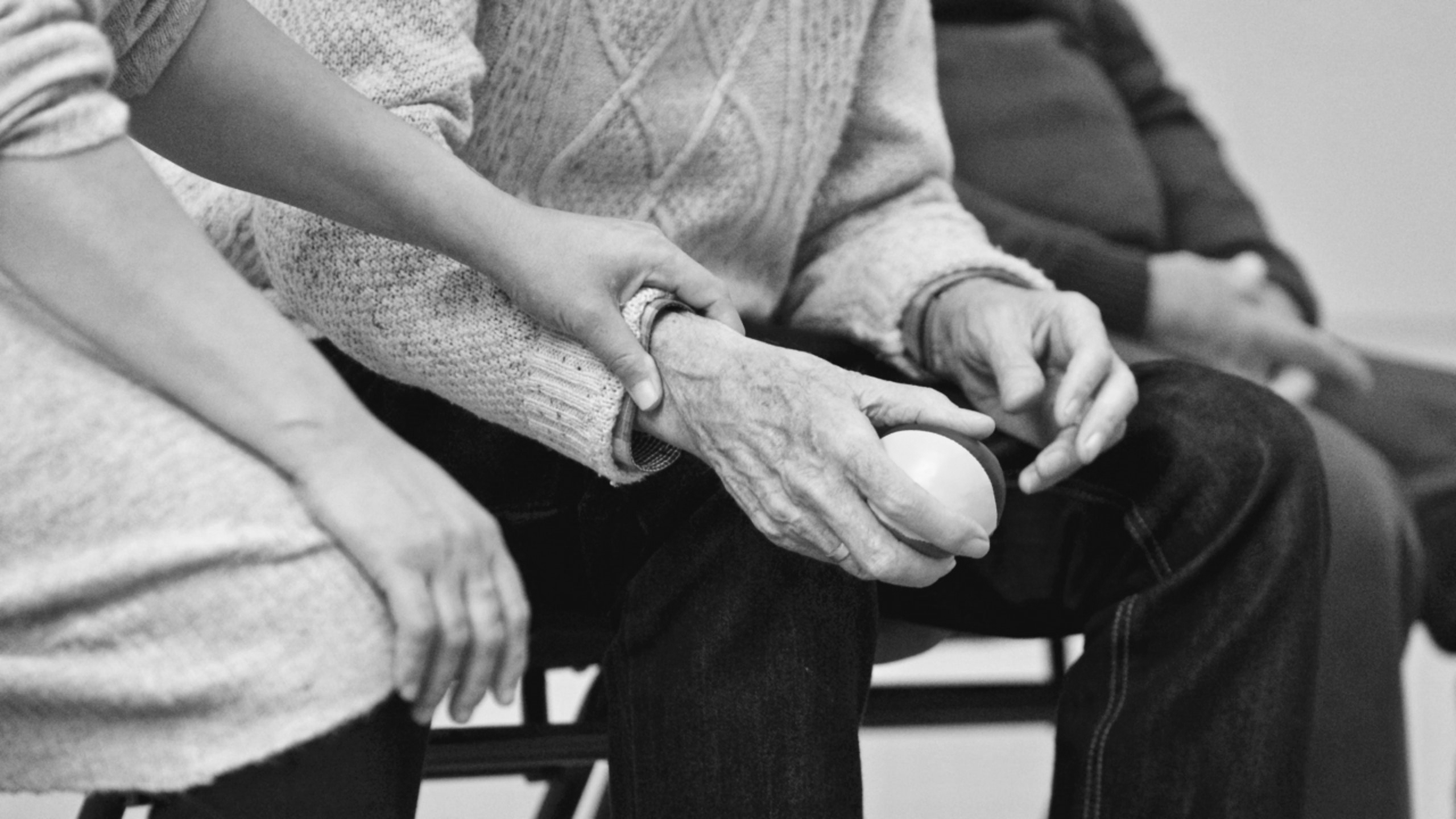 nurse taking senior woman's pulse as she holds a ball sitting by her husband