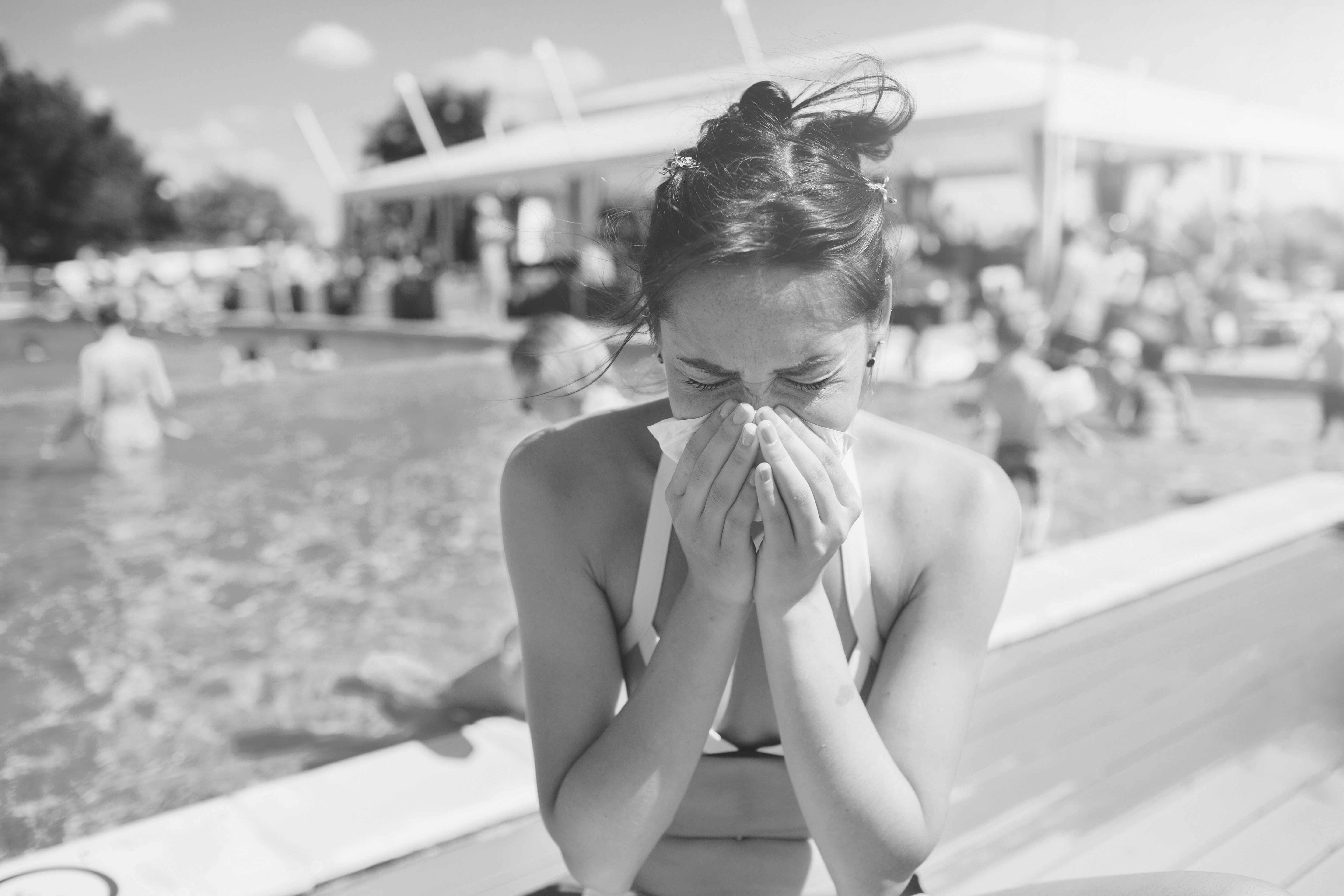 woman sneezing by swimming pool due to allergies