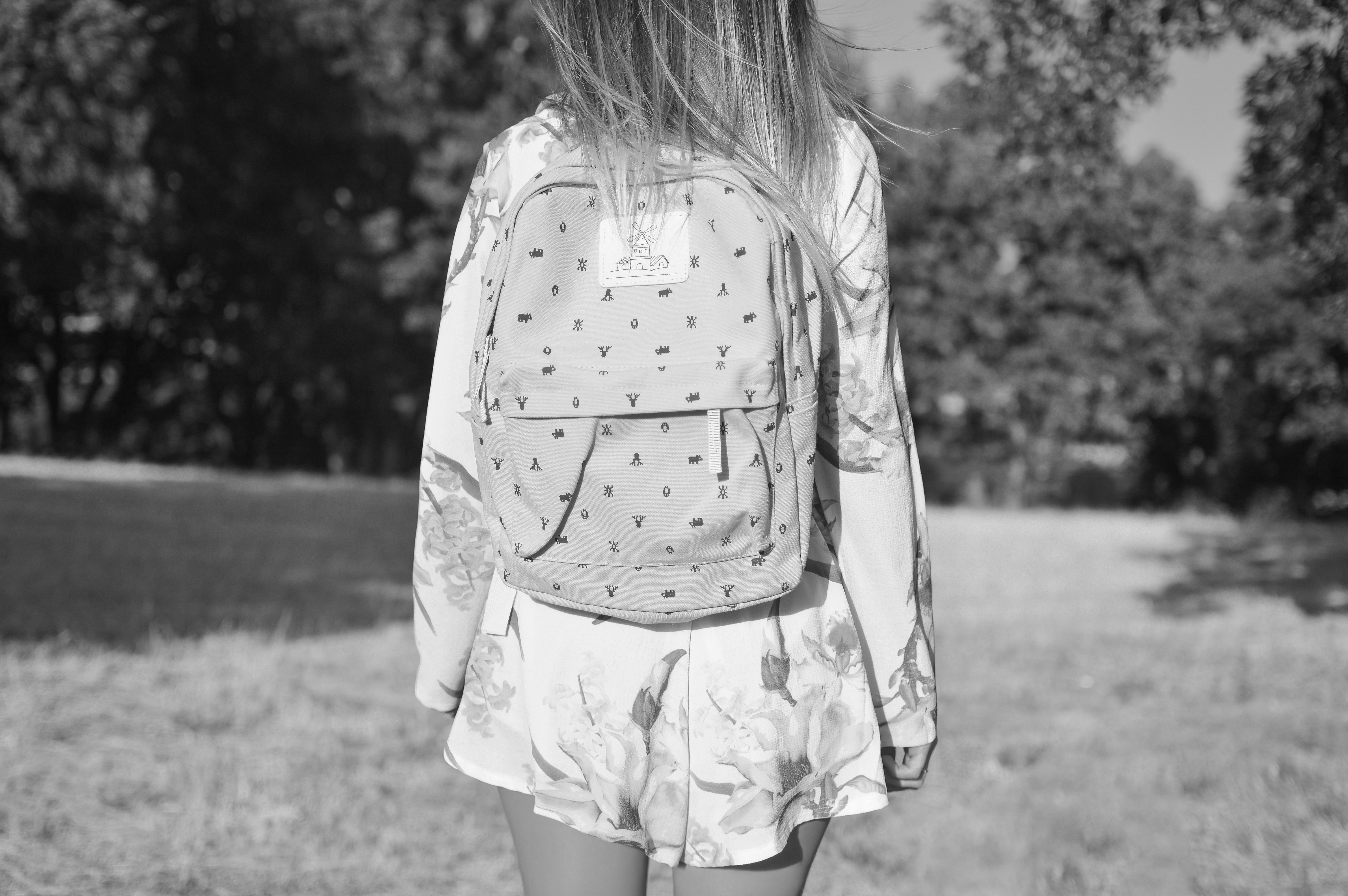 person walking in field with trees wearing dress and backpack