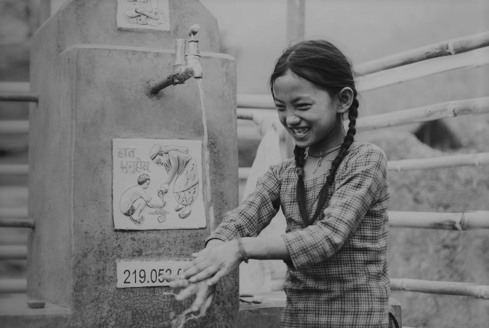 child in third world country washing hands with clean water pouring from pipe with instructions in native language