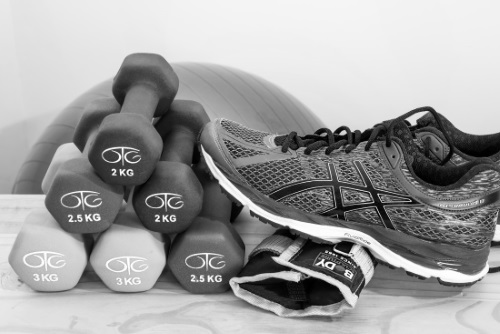 stack of 2kg to 3kg dumbells next to new running shoe and brace with exercise ball in background