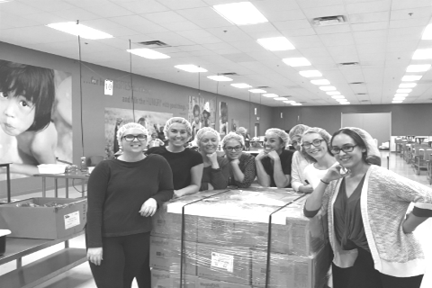 volunteers from AFC Chiropractic posing with large shipment of donations