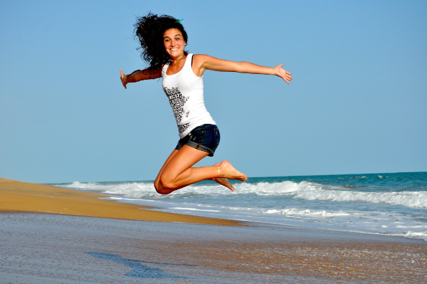 feeling healthy, a fit woman jumping for joy on an empty beach