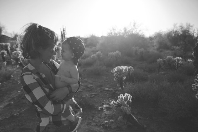 mom and baby hiking in the Arizona desert, looking in each other's eyes and smiling