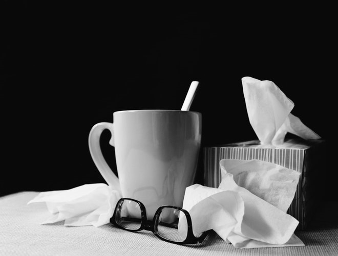 mug of tea with tissue box and upside down pair of glasses, loose tissues on the table
