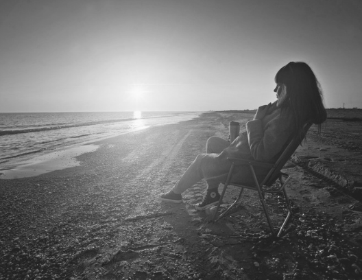 woman sitting on beach watching the ocean at sunrise