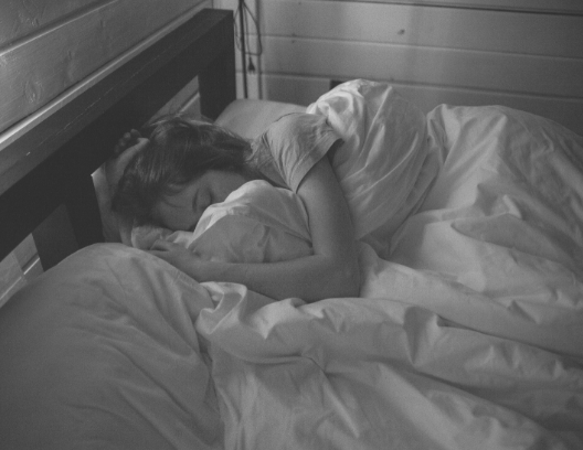 woman nestled in bed under comforter, sleeping comfortably