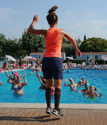 Water aerobics exercise group doing guided aerobic exercise in an outdoor pool